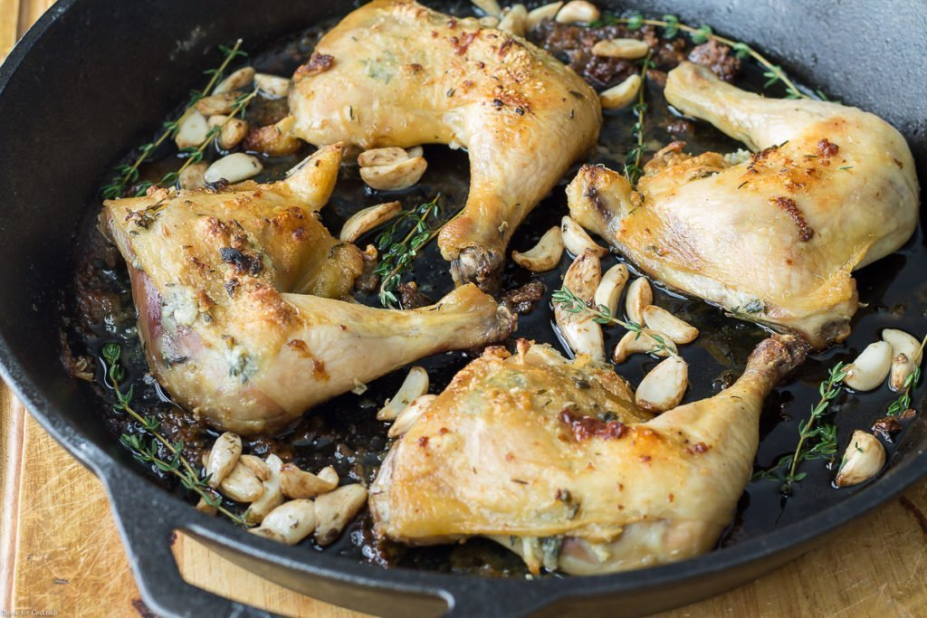 Horizontal side view view of easy roast chicken quarters with thyme and roasted garlic in cast iron skillet