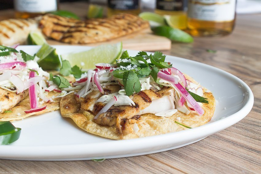 Beer Marinated Grilled Fish Tacos, these classic tacos are topped with shredded cabbage, radishes, pickled red onions, jalapeno slices, and cojita cheese.
