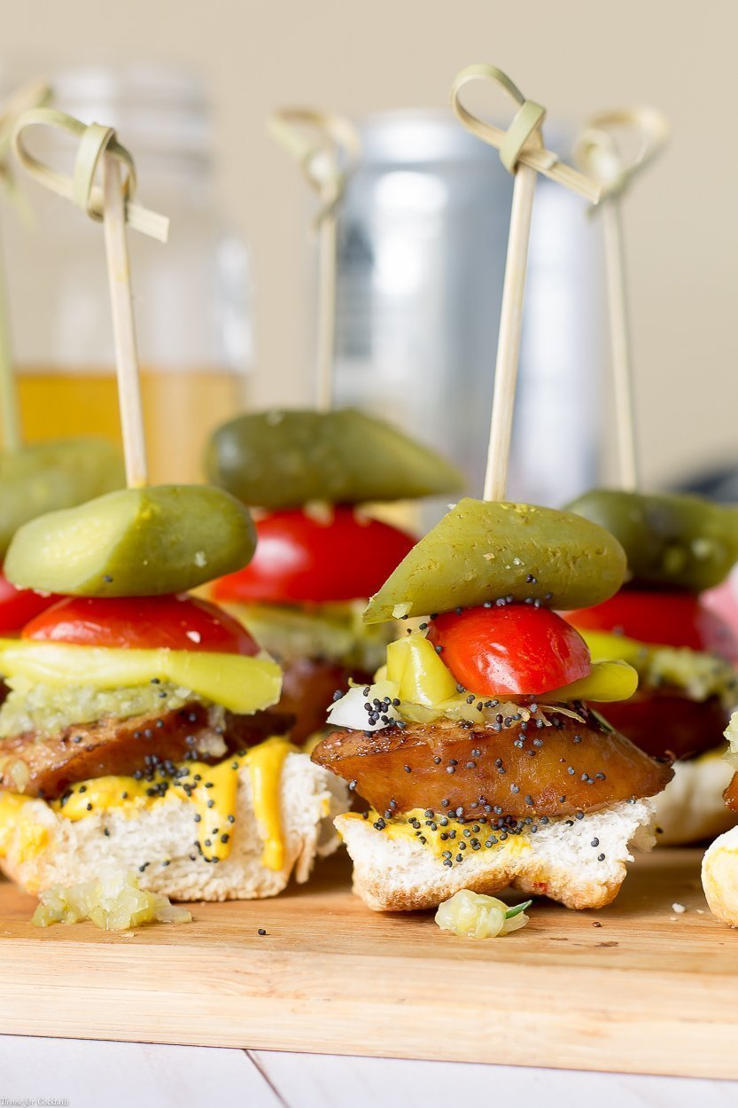 toasted bun, thick slice of smoked sausage, sweet relish, white onion, yellow mustard, pickle spear, sesame seeds, all in one bite on a skewer, vertical closeup #2