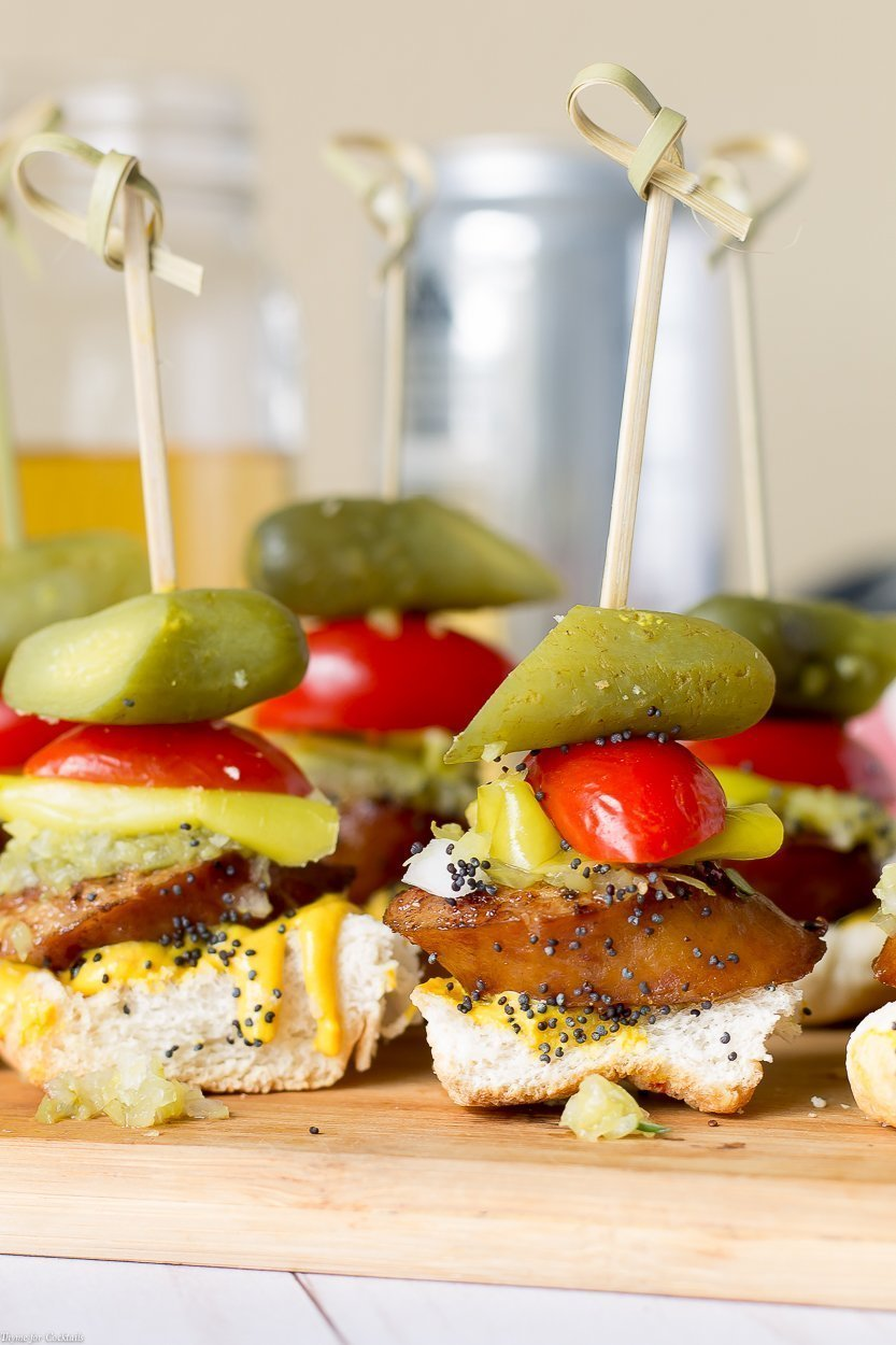 toasted bun, thick slice of smoked sausage, sweet relish, white onion, yellow mustard, pickle spear, sesame seeds, all in one bite on a skewer, vertical close up