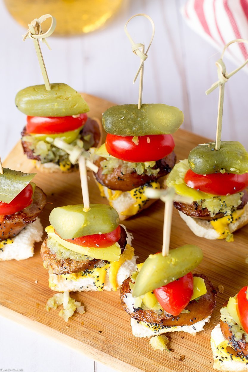 toasted bun, thick slice of smoked sausage, sweet relish, white onion, yellow mustard, pickle spear, sesame seeds, all in one bite on a skewer, overhead shot