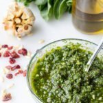 vertical close of Spinach Cranberry Pesto recipe in bowl with olive oil bottle in background
