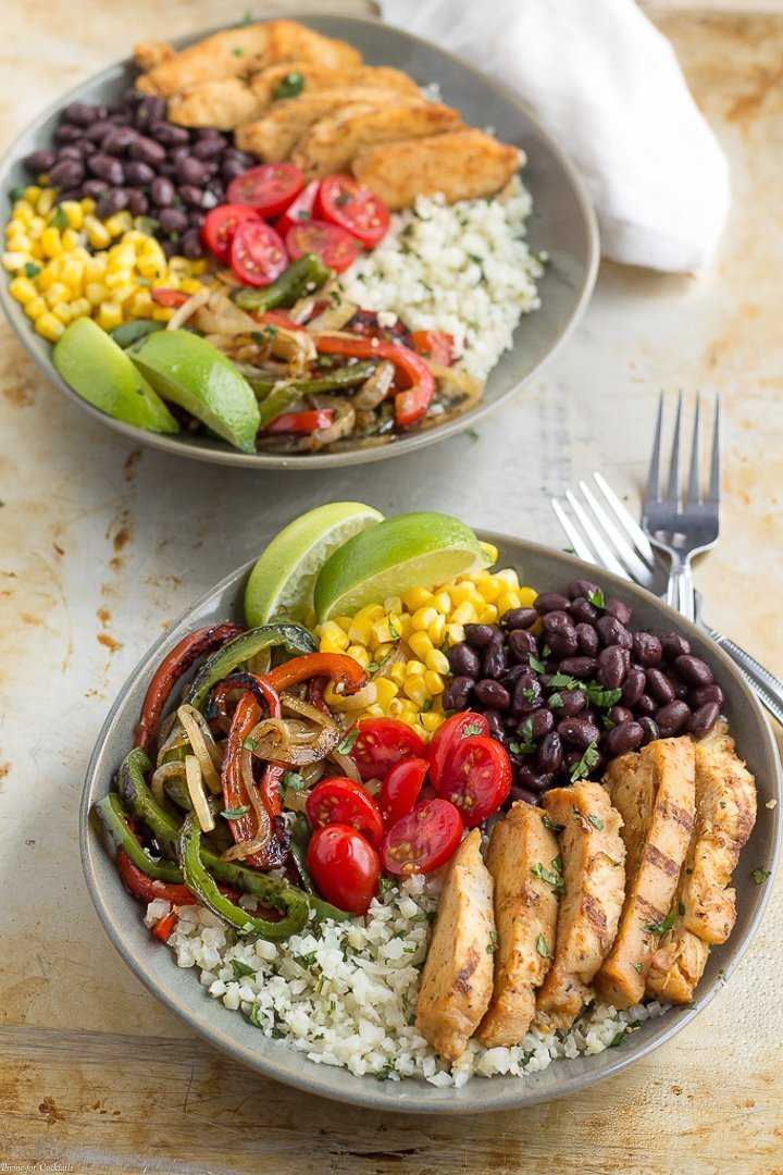 15-Minute Chicken Fajita Cauliflower Rice Bowls - two bowls of cilantro lime cauliflower rice topped with grilled chicken, black beans, corn, grilled onions and peppers plus fresh tomatoes