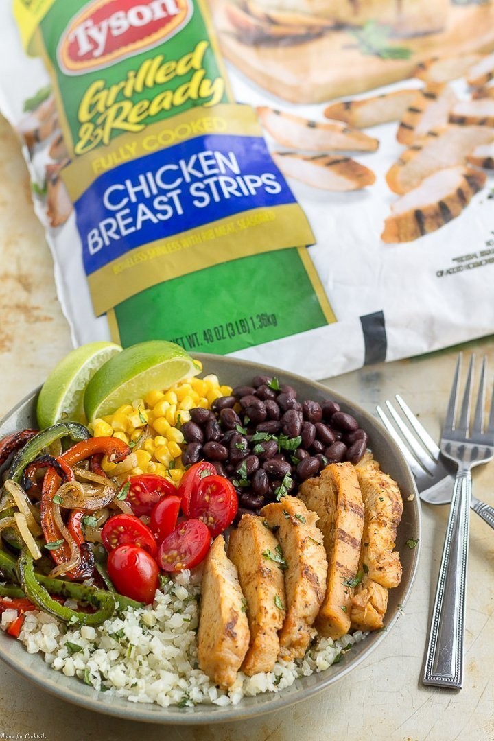 15-Minute Chicken Fajita Cauliflower Rice Bowls - bowl of cilantro lime cauliflower rice topped with grilled chicken, black beans, corn, grilled onions and peppers plus fresh tomatoes - Tyson bag in background