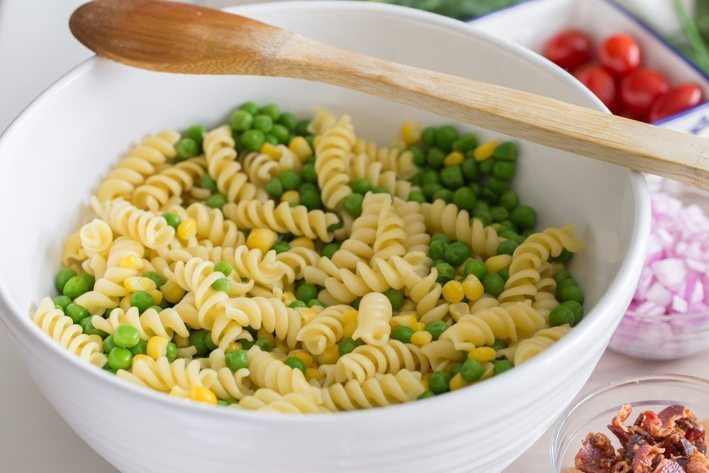 big white bowl of cooked rotini pasta with thawed frozen peas and corn for Loaded Fried Chicken Pasta Salad