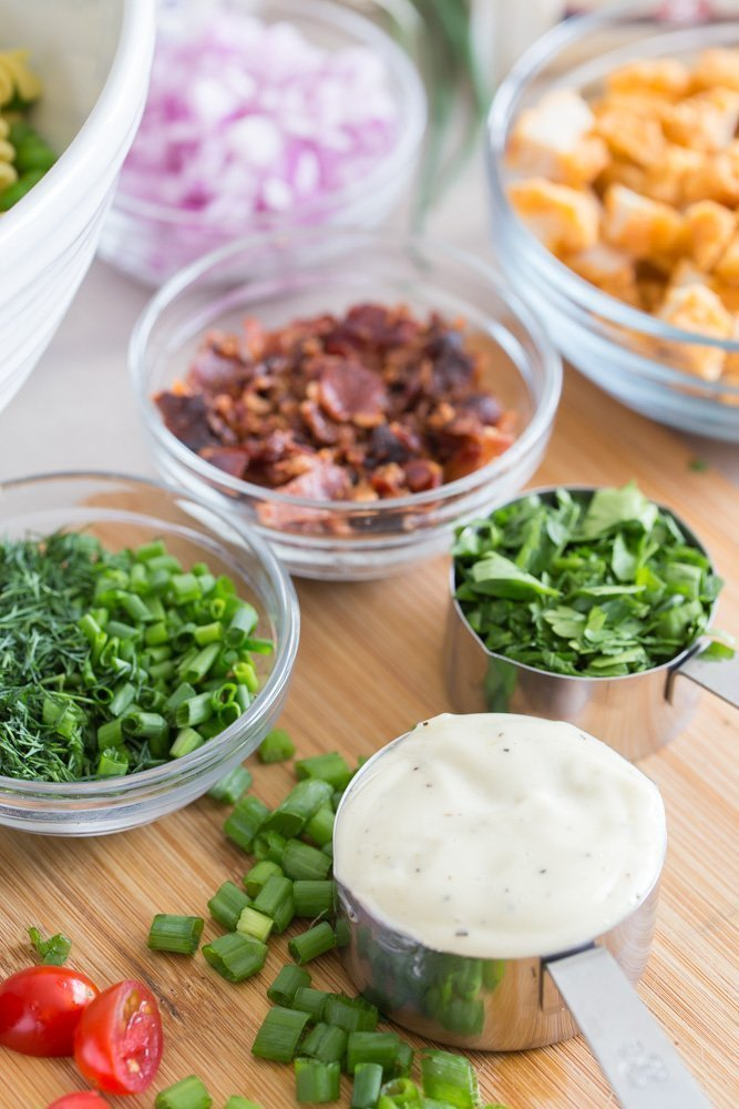 bowls of bacon, herbs, and creamy garlic dressing for Loaded Fried Chicken Pasta Salad